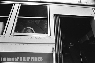 Little girl peeping out of a bus window.