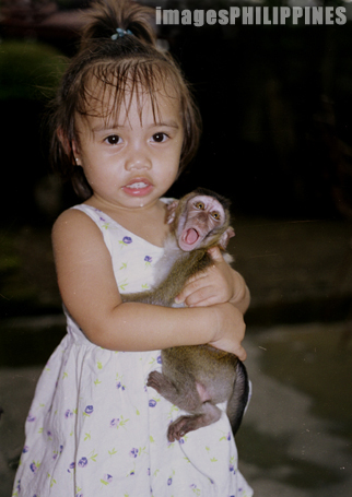 """""""Young Girl holding a monkey"""",  Place Taken: Taal, Batangas take on  Date Taken: 2002"""