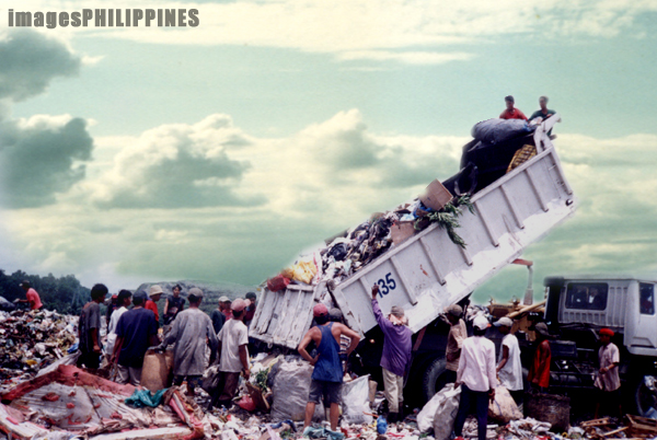 """Scavengers waiting for new trash from a dump truck in 