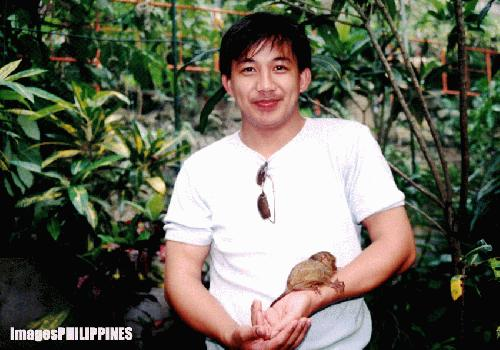 """A Tourist with tarsier in his arm"", 