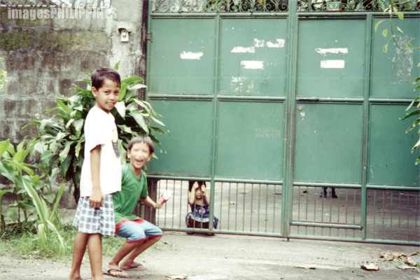 """Batangueno children playing near a church"", 